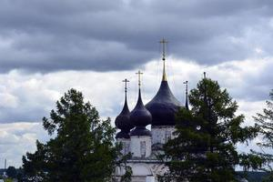cupole della chiesa con croci contro il cielo blu. tempio di pietra bianca tra gli alberi. foto