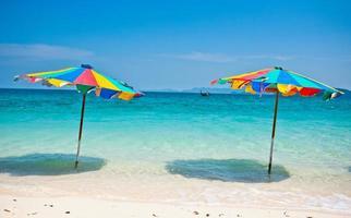 sedia a sdraio sotto l'ombrellone di colorati sulla spiaggia phuket, thailandia foto