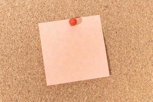 nota vuota e puntina a pressione sulla bacheca di sughero. modello per testo o disegni dell'annuncio foto
