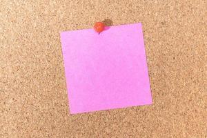 nota rosa vuota e puntina a pressione sulla bacheca di sughero. modello per testo o disegni dell'annuncio foto