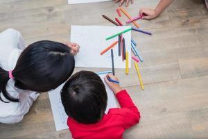 gruppo di studenti in età prescolare e insegnanti che disegnano su carta in classe d'arte. torna al concetto di scuola e istruzione. tema persone e stili di vita. stanza dell'asilo foto