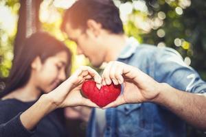 due mani di giovani amanti o coppie che tengono il filo rosso del cuore in mezzo allo sfondo naturale all'aperto per san valentino. concetto di vacanza e relax. festa di celebrazione della luna di miele e anniversario di matrimonio foto