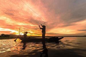 silhouette pescatore pesca utilizzando rete sulla barca al mattino in thailandia, natura e cultura concept foto