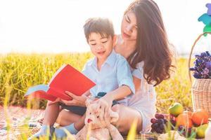 piccolo ragazzo asiatico e sua madre che leggono libri quando fanno picnic nel prato. madre e figlio che imparano insieme. festeggiando la festa della mamma e apprezzando il concetto. persone estive ed educazione allo stile di vita foto