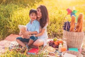 bella madre asiatica e figlio che fanno picnic e nella festa estiva di pasqua sul prato vicino al lago e alla montagna. vacanza e vacanza. stile di vita delle persone e concetto di vita familiare felice. persona tailandese foto