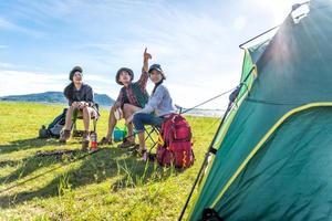 gruppo di escursionisti che guardano il punto di vista dell'attrazione al campo di prato con sfondo di montagna e lago. concetto di persone e stili di vita. tema di escursioni e viaggi. tre persone con zaino. tenda in primo piano foto