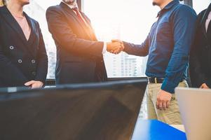 concetto di handshake di riunione di partenariato commerciale. uomini d'affari che fanno stretta di mano. uomini d'affari di successo contraggono la stretta di mano dopo aver finito di trattare con lo sfondo della costruzione di finestre del grattacielo foto
