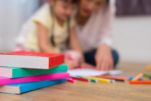 primo piano di libri e colori pastello sul pavimento con sfondo mamma e bambini. torna al concetto di apprendimento dell'educazione scolastica e artistica. tema bambini e insegnanti foto