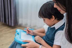 mamma asiatica che insegna a un ragazzo carino a disegnare insieme la lavagna. torna al concetto di scuola e istruzione. tema della famiglia e della casa dolce casa. tema per bambini in età prescolare foto