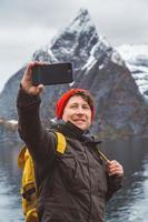 uomo viaggiatore ritratto che scatta autoritratto una foto con uno smartphone sullo sfondo di una montagna