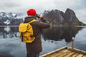 uomo che parla al telefono cellulare in uno zaino giallo in piedi sullo sfondo di una montagna e di un lago foto