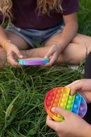 le ragazze giocano a un tocco di silicone colorato popolare pop-it foto