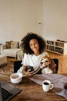 donna di colore che usa il cellulare e abbraccia il suo cane mentre fa colazione foto