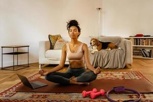 giovane donna nera che medita durante la pratica dello yoga con il suo cane foto