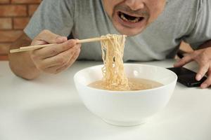 l'uomo tailandese casual affamato usa le bacchette per mangiare spaghetti istantanei caldi in una tazza bianca durante le pause pranzo, veloci, gustosi ed economici. pasto fast food asiatico sano tradizionale dello stile di vita giapponese e cinese. foto