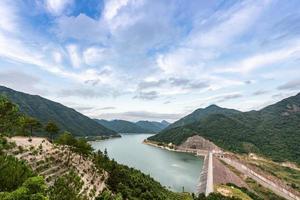 il serbatoio in montagna in una giornata di sole ha il cielo azzurro e l'acqua limpida foto
