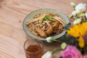 una ciotola di zuppa di noodle con salsiccia, verdure e carne è sul tavolo foto