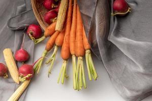 i ravanelli rossi e arancioni sono sul panno bianco foto