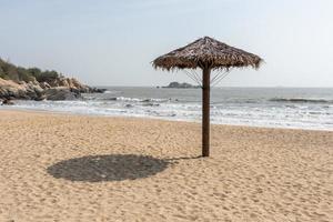 ci sono ombrelloni in erba sulla spiaggia in estate foto