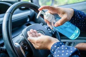 nuova normale donna lavoratrice asiatica che si lava le mani premendo gel igienizzante alcol blu per proteggere la sicurezza del coronavirus in auto foto