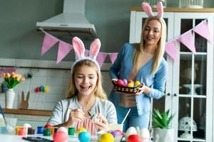la ragazza allegra sta dipingendo le uova di Pasqua. la mamma tiene in mano un cesto con le uova di Pasqua. foto