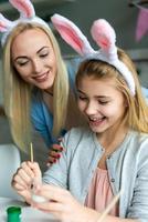 la mamma e la figlia sorridenti dipingono le uova di Pasqua nelle orecchie del coniglietto. foto