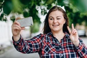 bella ragazza sorridente che mostra un gesto di pace mentre si fa un selfie isolato sullo sfondo della città foto