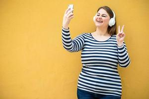 sullo sfondo di un muro arancione, una donna allegra e sorridente mostra un gesto di pace e si fa un selfie su uno smartphone foto