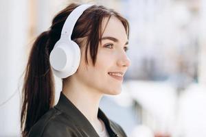 foto di una bella donna allegra che indossa le cuffie tecnologia moderna in piedi sullo sfondo della città