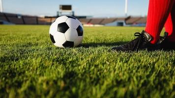 giocatore di calcio o di calcio in piedi con la palla sul campo per calciare il pallone da calcio allo stadio di calcio foto