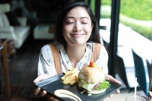 donne asiatiche sorridenti e felici e si divertivano a mangiare hamburger al caffè e al ristorante in tempo di relax foto