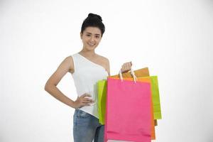la bella ragazza delle donne asiatiche tiene in mano le borse della spesa e sorride foto