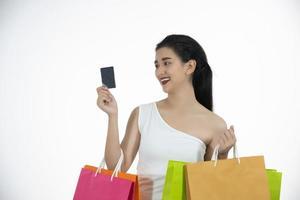 donne asiatiche e bella ragazza tiene in mano le borse della spesa e usa uno smartphone e sorride mentre fa shopping e compra con carta di credito foto
