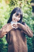 belle giovani donne asiatiche che fanno la forma del cuore con le mani e sorridono felici nell'amore all'aperto foto