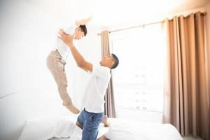 felice famiglia asiatica con figlio a casa in camera da letto che gioca e ride foto
