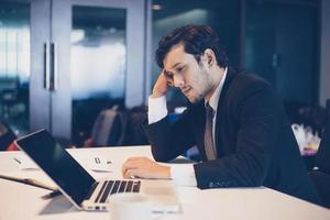 uomo d'affari serio per il duro lavoro svolto fino al mal di testa foto
