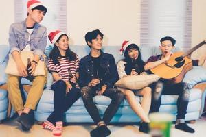 gruppo asiatico di amici che fanno festa con bevande alcoliche e giovani che si divertono in un bar che tostano cocktail.soft focus foto