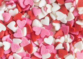 le forme di cuore rosse bianche e rosa spruzzano lo sfondo foto