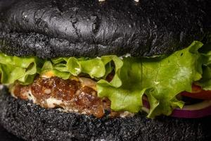 gustoso hamburger fatto in casa alla griglia con manzo, pomodoro, formaggio, cetriolo e lattuga foto