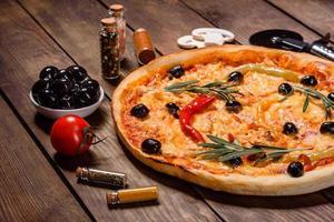 gustosa pizza calda fresca su uno sfondo scuro. pizza, cibo, verdura, funghi foto