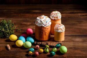 torta di pasqua e uova colorate su sfondo scuro foto