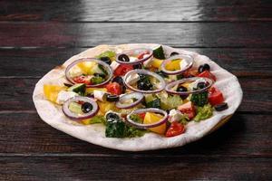 gustosa insalata greca fresca su una pita cotta per una tavola festiva foto