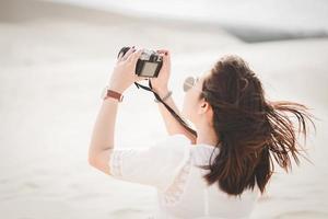 viaggio e fotografia. giovane donna con la macchina fotografica che prende foto alle dune di sabbia bianca, vietnam