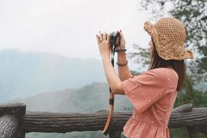 giovane bella donna asiatica viaggiatrice che utilizza la fotocamera digitale compatta e sorride, guardando lo spazio della copia. stile di vita viaggio viaggio, esploratore di viaggi mondiali o concetto di turismo estivo in asia foto