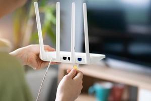 ragazza asiatica sta collegando il cavo di rete al trasmettitore wifi foto