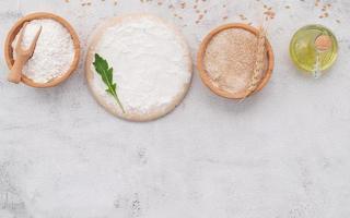 gli ingredienti per l'impasto della pizza fatta in casa con spighe di grano, farina di grano e chicchi di grano allestiti su sfondo bianco di cemento. foto