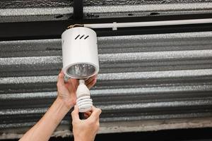 mano umana sta rimuovendo una lampadina fluorescente in una plafoniera circolare per trasformarla in una lampadina a led. foto