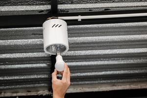 mano umana sta installando una lampadina a led in una plafoniera circolare. foto