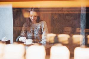 donna sorridente al bar utilizzando il telefono cellulare e messaggiando nei social network, seduta da sola foto
