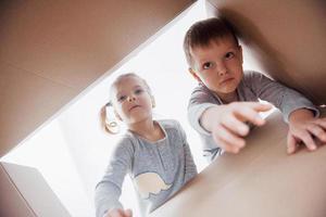 due bambini piccoli ragazzo e ragazza che aprono una scatola di cartone e guardano dentro con sorpresa foto